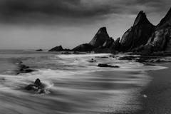 Landscape seascape of jagged and rugged rocks on coastline with long exposure Stock Photos