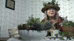 Pan shot of grandma surrounded with plants sitting at the table Stock Footage