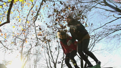 Girls shot from low angle throw leaves and jump from a bench Stock Footage