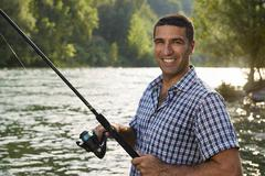 portrait of man fishing on river and holding rod - stock photo