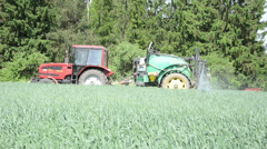 Farmer driving tractor fertilizer spray nozzles along forest Stock Footage