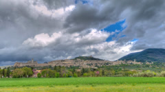 Assisi, Italy at distance in time lapse as storm clouds roll overhead, - stock footage