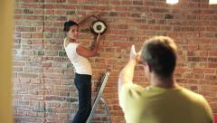 Couple hanging a clock on the brick wall in their new flat Stock Footage