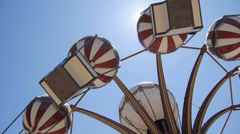 Attraction in amusement park spinning over the sun - stock footage