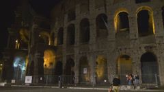 Famous Colosseum forum Rome night people walk illuminated wall building ancient Stock Footage