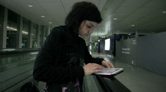 Young Woman using tablet pc on moving escalator at aitport - stock footage