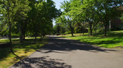 Path through tree covered campus Stock Footage