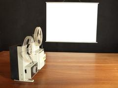 Film projector aimed at the screen hangs on a black wall Stock Photos