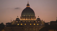 Rome closeup San Pietro cupola dome illuminated night twilight orange sky dusk Stock Footage