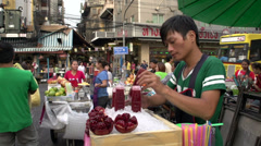 Man selling fresh fruit juice in China town Bangkok Stock Footage