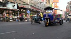 Busy street with a pan following a tuk tuk in China town Bangkok Stock Footage