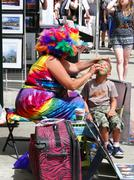 Colorful artist doing face paint for child Stock Photos
