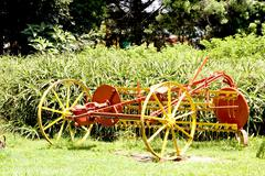 Restored vintage farm implement painted yellow and red Stock Photos