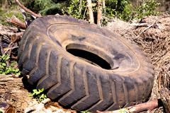 Used obsolete tractor tire lying on pile of debris Stock Photos