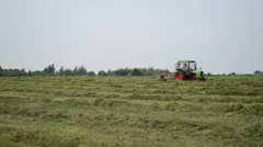 Tractor turning raking cut hay in field Stock Footage