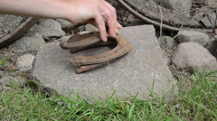 Hand make stack of rusty retro horse shoes on stones background Stock Footage