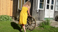 Girl in yellow dress rolls old carriage wheel near rural house Stock Footage