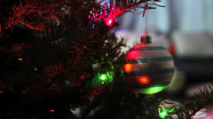Christmas ornament spins on tree branch with lights Stock Footage