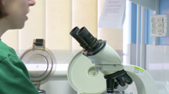 Female Scientist using a microscope Stock Footage