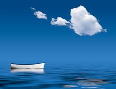 old rowing boat marooned at sea - stock photo