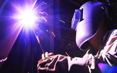Industrial worker make a spark welding Stock Photos