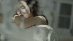Beautiful brunette model wearing lingerie relaxing in her boudoir. - stock footage