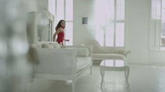 Beautiful brunette in red evening gown runs to look out of her apartment window - stock footage