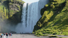 Group of tourists at Skogafoss waterfall on a sunny day, Iceland Stock Footage