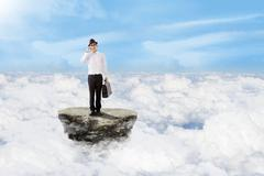 businessman on the phone above clouds - stock photo
