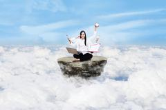 entrepreneur multitasking above clouds - stock photo