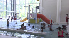 Kids at indoor swimming pool Stock Footage