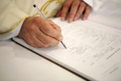 Priest signing the marriage register Stock Photos