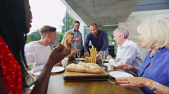Happy group of family & friends eating together and drinking wine in modern home Stock Footage