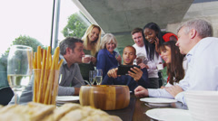 Cheerful diverse adult group gather round to look at screen of a computer tablet Stock Footage