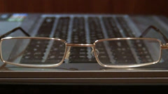 Glasses lying on a keyboard Stock Footage