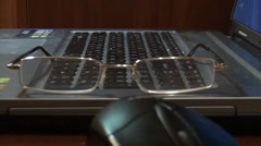 Mouse, glasses lie on a keyboard Stock Footage