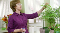 Mature woman tending to her plants Stock Footage