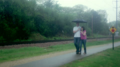 Young couple (man and woman), walking along a trail in the rain - stock footage