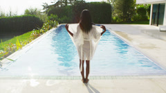 Beautiful woman outside modern home slips out of her robe for a swim in the pool Stock Footage