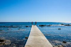 wooden bridge juts out into the expanse of the sea - stock photo
