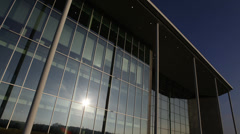 Time lapse of sun and clouds reflected on the windows of modern office building - stock footage