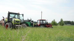 Workers on heavy field work tractors talk about field sprayers Stock Footage