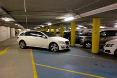 car badly parked in car park - stock photo