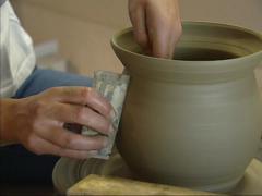 Ceramic clay on turntable - Ceramist shapes a vase - finishing Stock Footage