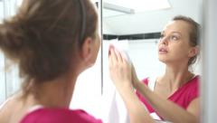 Young woman putting on make-up - stock footage
