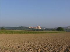 Plowed land + zoom in West front of Benedictine Abbey Stift Melk Stock Footage