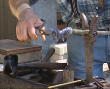 Glassblower at work, sculpting a glass animal Stock Footage