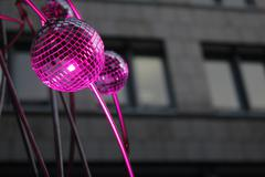 Pink spotlighted mirror balls in front of dark stony business building Stock Photos