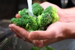 Man's hands washing broccolli vegetables in kitchen sink Stock Photos
