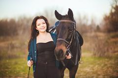 young woman with a horse on nature - stock photo